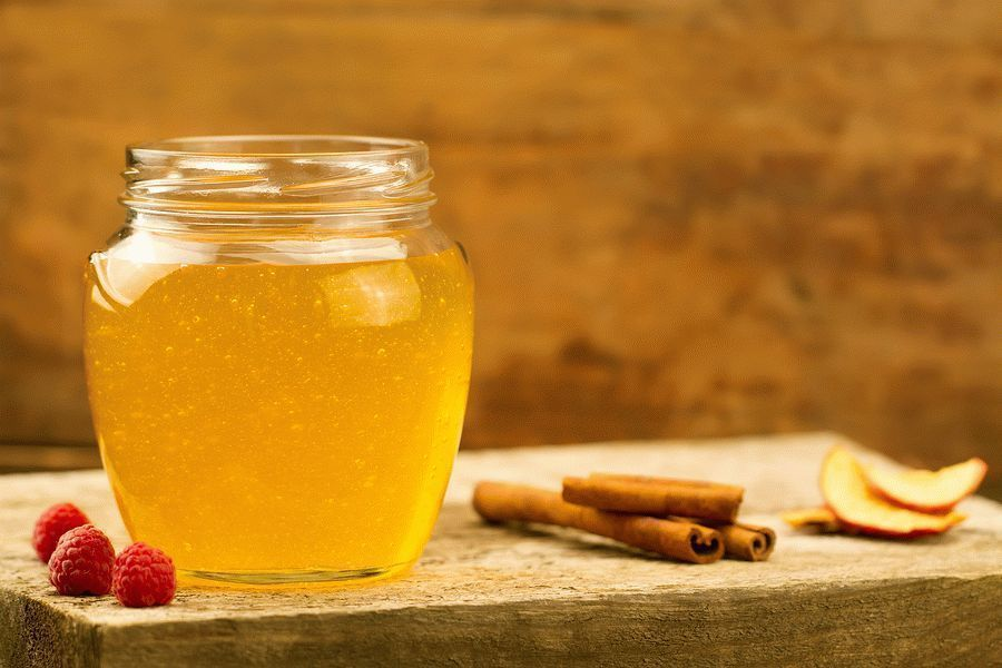 glass jar of Linden honey with drizzler cinnamon raspberries apples on wooden background